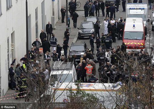 У здания напротив офиса редакции «Charlie Hebdo» на улице Никола Аппер, 10 – море цветов и горящих свечей…
